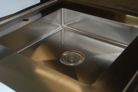 stainless steel integral sink with bottom sloped to a die lowered three and a half inch drain